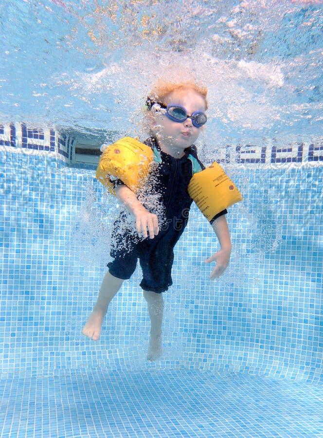 Junger Junge, der in einen Swimmingpool springt stockfotografie