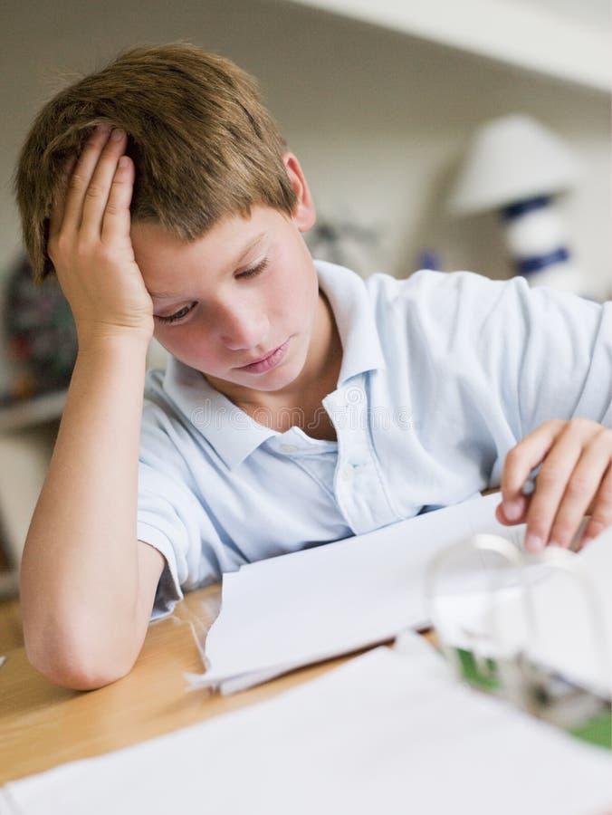 Junger Junge, der Heimarbeit in seinem Raum tut lizenzfreies stockfoto