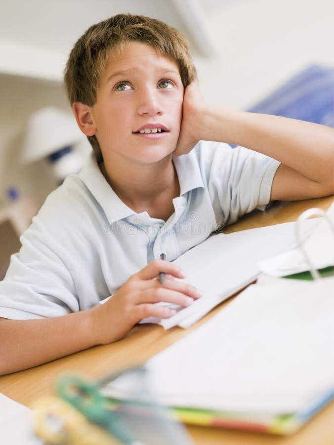 Junger Junge, der Heimarbeit in seinem Raum tut lizenzfreie stockfotografie