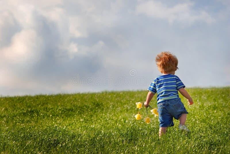 Junger Junge, der herauf einen Hügel geht stockfotos