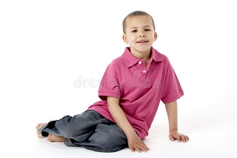 Junger Junge, der im Studio sitzt stockfotos