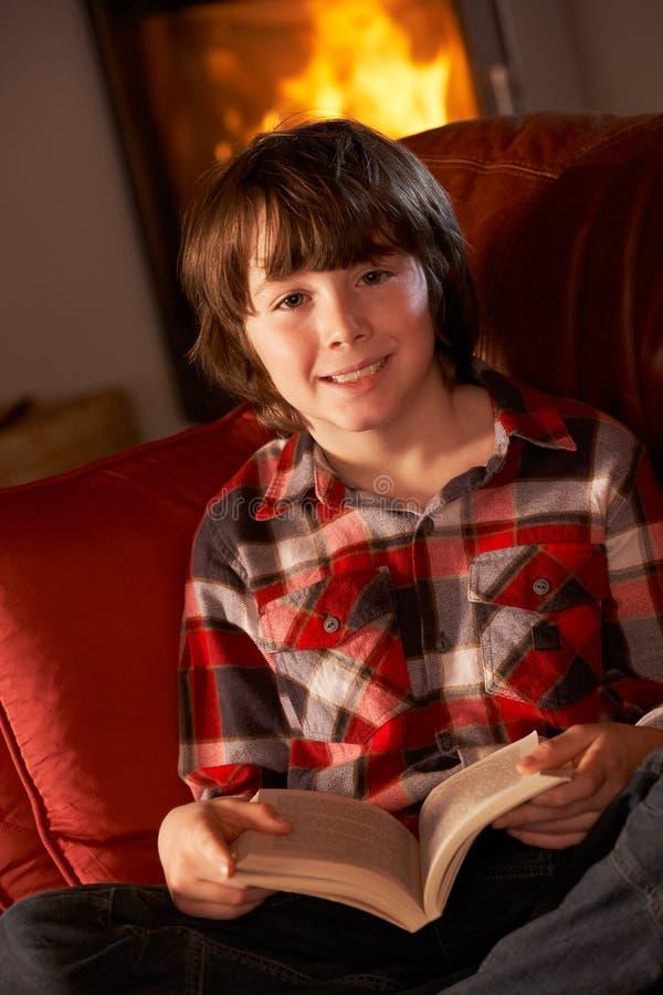 Junger Junge, der mit Buch durch Cosy Protokoll-Feuer sich entspannt stockfotos