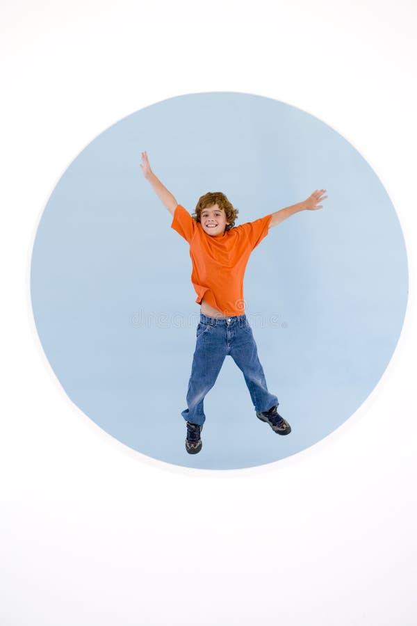 Junger Junge, der mit den heraus lächelnden Armen springt stockbilder