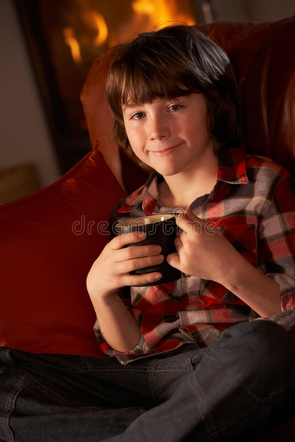Junger Junge, der mit heißem Getränk durch Cosy Protokoll-Feuer sich entspannt lizenzfreie stockfotografie