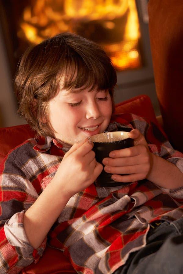 Junger Junge, der mit heißem Getränk durch Cosy Protokoll-Feuer sich entspannt lizenzfreie stockbilder
