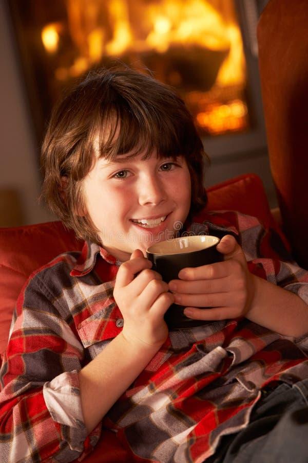 Junger Junge, der mit heißem Getränk durch Cosy Protokoll-Feuer sich entspannt stockfotos