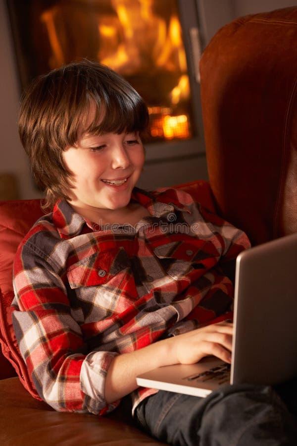 Junger Junge, der mit Laptop durch Cosy Protokoll-Feuer sich entspannt lizenzfreies stockbild