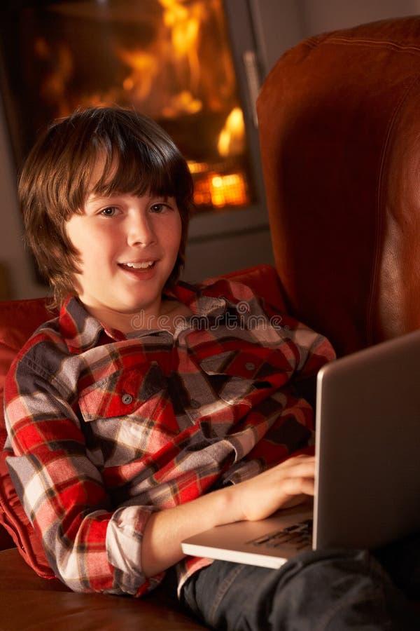 Junger Junge, der mit Laptop durch Cosy Protokoll-Feuer sich entspannt stockbild