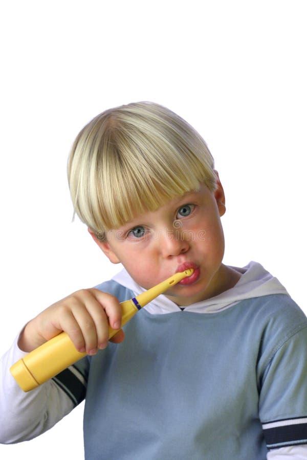 Junger Junge, der seine Zähne säubert stockfotografie