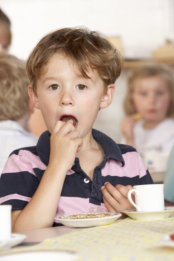 Junger Junge, der Tee an Montessori/am Vortraining trinkt stockfotos