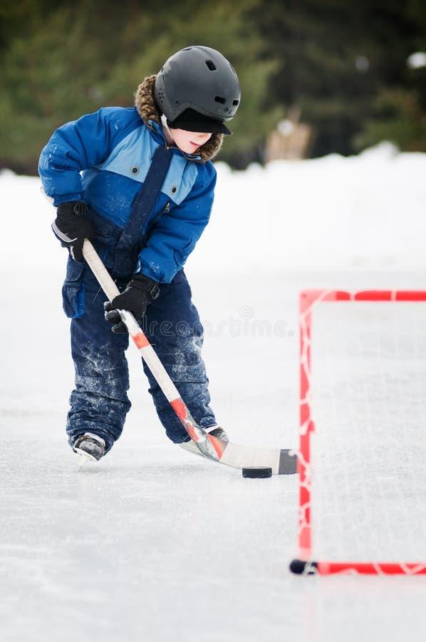 Junger Junge, der Teichhockey spielt stockbild