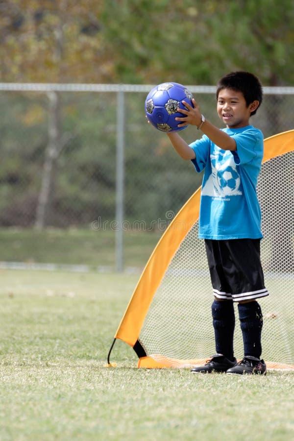 Junger Junge, der Tormann im Fußball spielt lizenzfreie stockfotografie