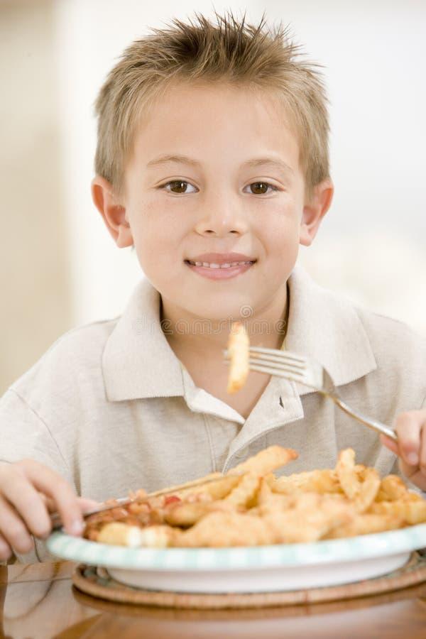 Junger Junge, der zuhause Fisch und isst lizenzfreie stockfotos