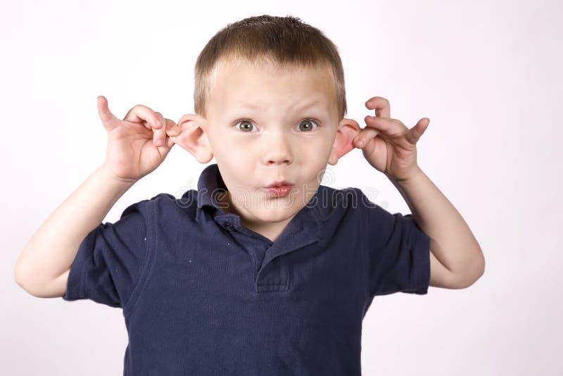 Junger Junge des Ausdrucks, der Ohren zieht lizenzfreie stockfotografie