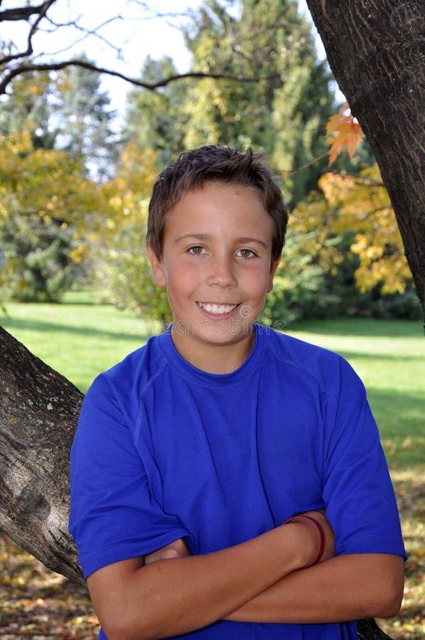 Junger Junge durch Baum im Herbst stockbild