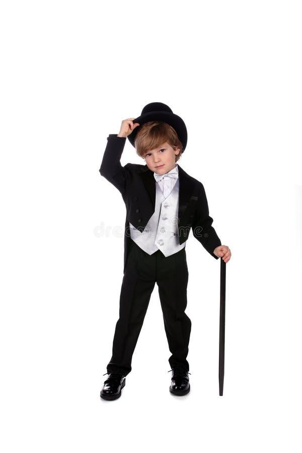 Junger Junge im Smoking, der seinen Hut spitzt lizenzfreie stockfotografie
