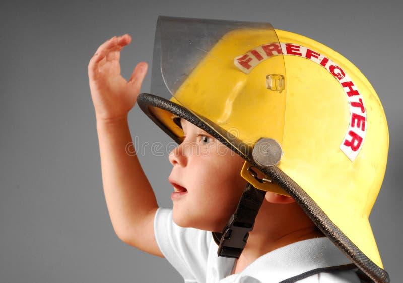 Junger Junge im Sturzhelm des Feuerwehrmannes stockfotografie