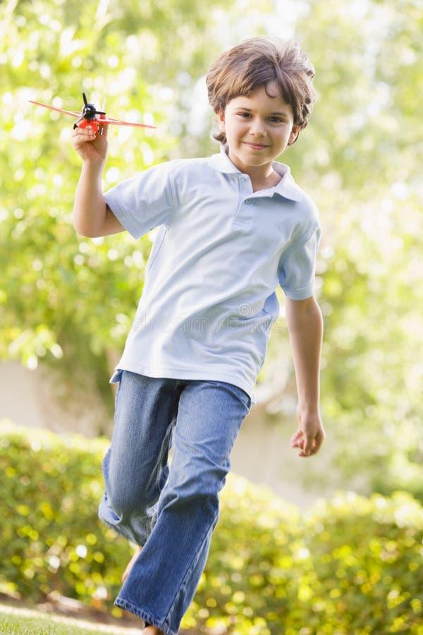 Junger Junge mit dem Spielzeugflugzeug, das draußen läuft stockfoto