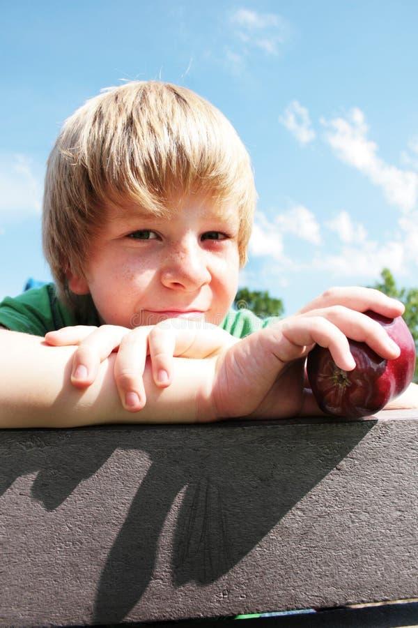 Junger Junge mit einem Apfel lizenzfreie stockbilder