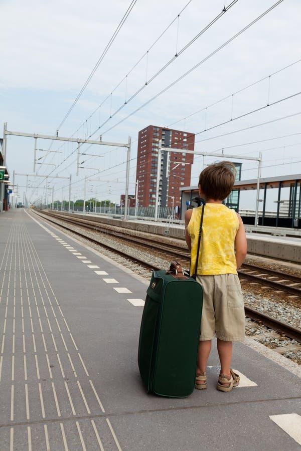 Junger Junge mit Gepäckwarteserie stockfoto