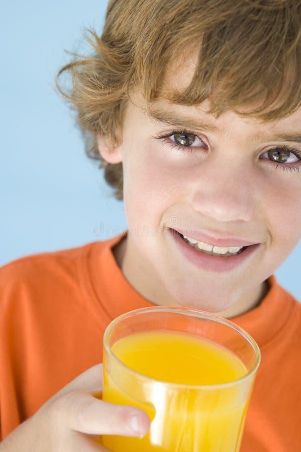 Junger Junge mit Glas des Orangensaftlächelns lizenzfreie stockbilder