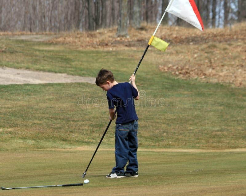Junger Junge mit Golf-Markierungsfahne stockbilder