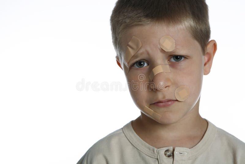 Junger Junge mit Pflastern auf Gesicht stockfotos