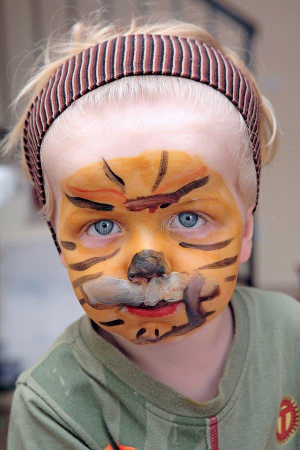Junger Junge oder Kleinkind abgedeckt im Tigergesichtslack stockbilder