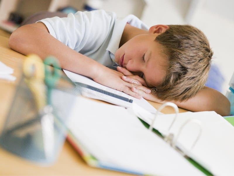 Junger Junge schlafend auf seinen Lehrbüchern stockfotos