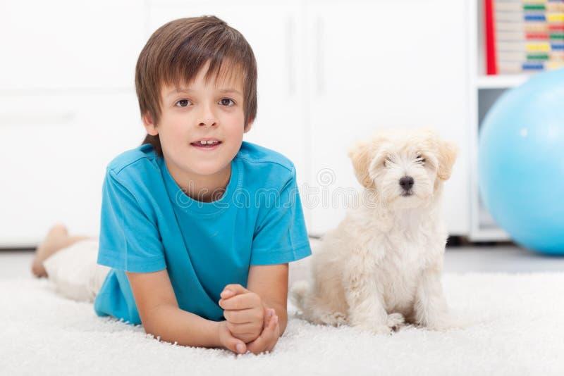 Junger Junge und sein gutes benehmendes Hündchen lizenzfreie stockbilder