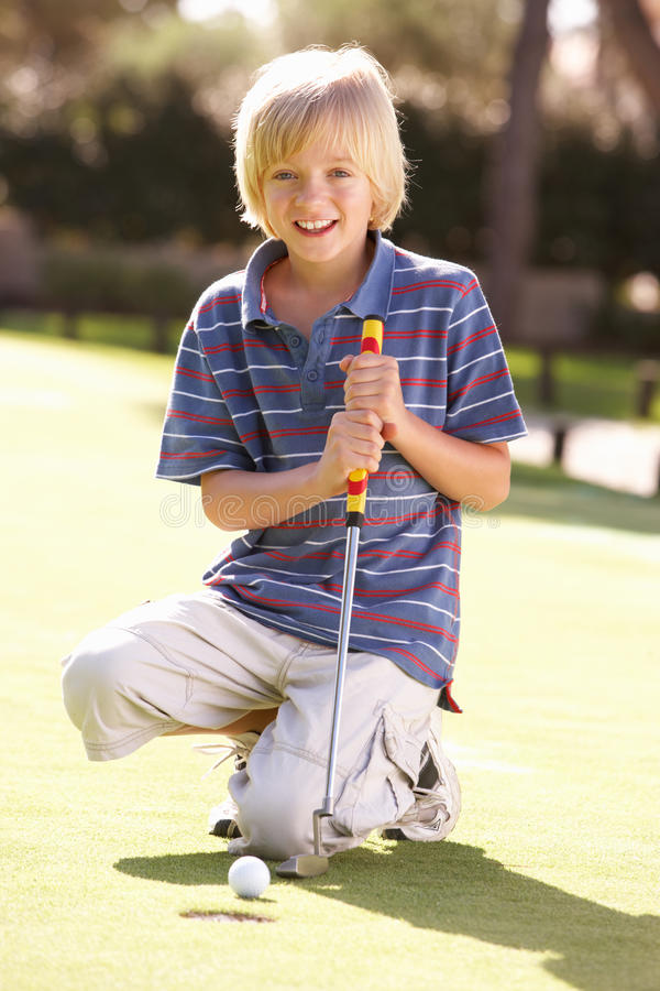 Junger Jungen-übendes Golf lizenzfreie stockfotos