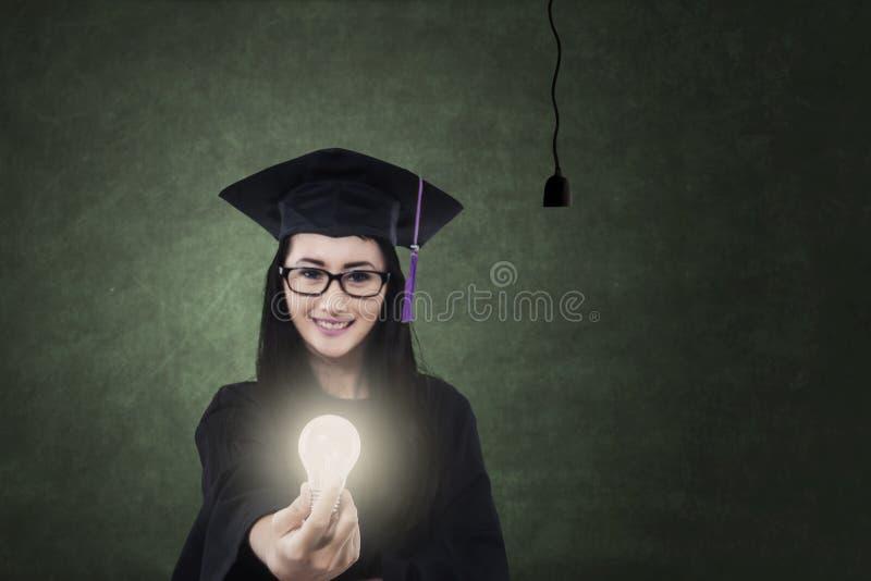 Junger Junggeselle, der helle Glühlampe gibt stockbild