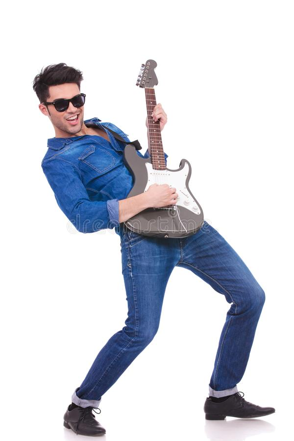 Junger kühler Gitarrist, der seine E-Gitarre spielt lizenzfreie stockbilder