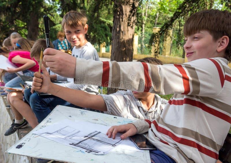 Junger Künstler bestimmt die Anteile mit einem Bleistift stockfotografie