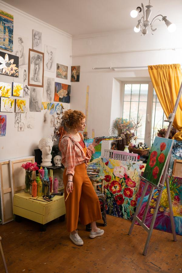 Junger Künstler, der die helle Kleidung steht nahe Segeltuch trägt lizenzfreie stockfotos