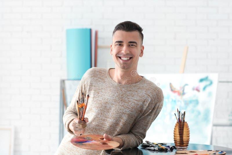 Junger Künstler mit Malerpinseln und Palette in der Werkstatt lizenzfreies stockfoto