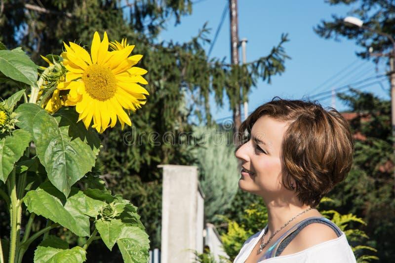 Junger kaukasischer Brunette und große Sonnenblume mit dem Marienkäfer stockfotografie