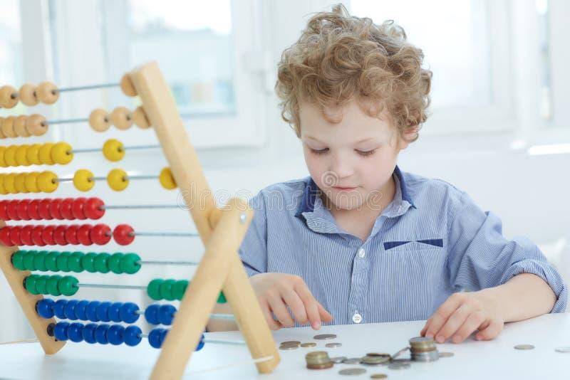 Junger kaukasischer gelockter Junge, der mit Zähler und Münzen spielt stockfoto