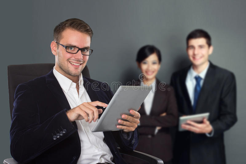 Junger kaukasischer Geschäftsmann, der einen Tabletten-PC, sein Personal auf Th hält stockbild