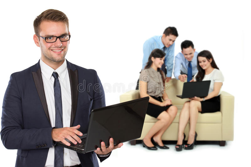 Junger kaukasischer Geschäftsmann, mit seinem Team hinter dem Halten des Laptops lizenzfreies stockfoto