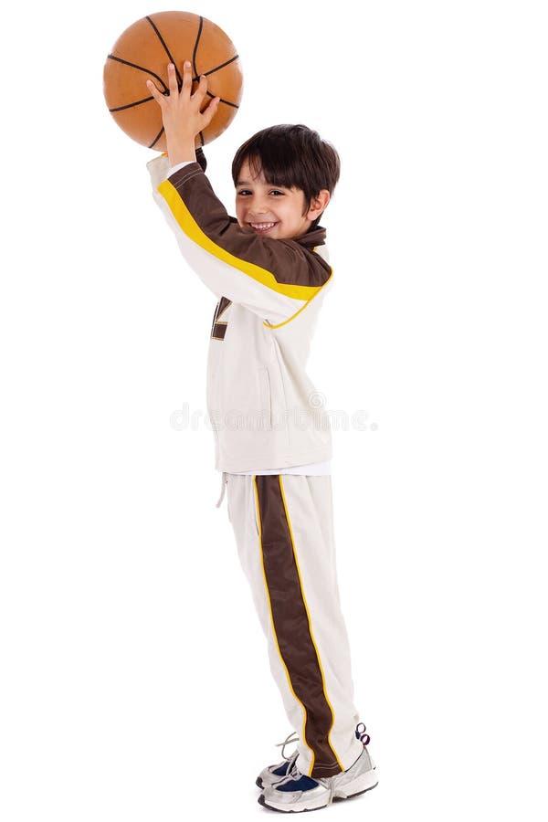 Junger kaukasischer Junge beim Spielen der Korbkugel stockfotos