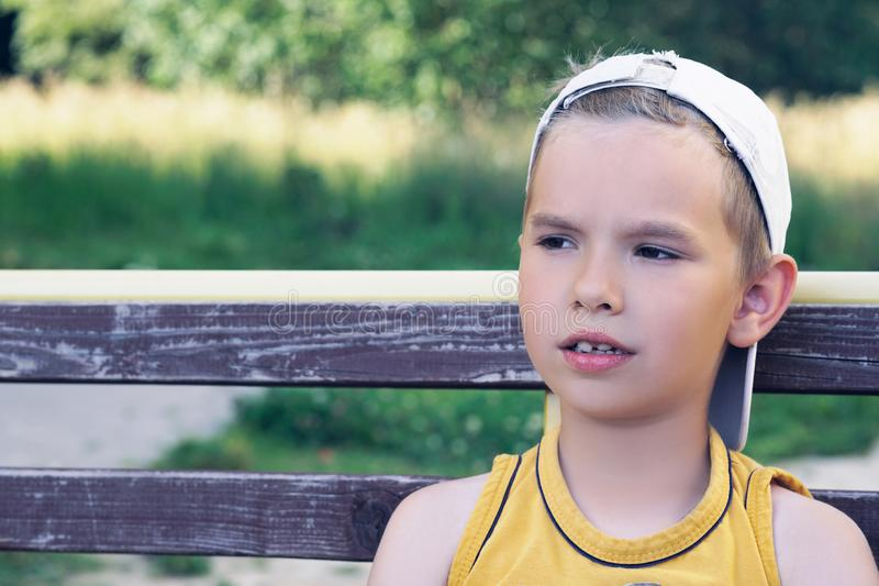 Junger kaukasischer Junge, der auf Bank am Park wartet auf seine Freunde sitzt lizenzfreies stockbild