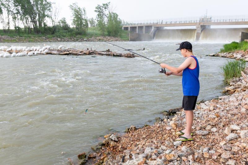 Junger kaukasischer Junge, der das Wasserverdammungsfischen bereitsteht lizenzfreie stockbilder