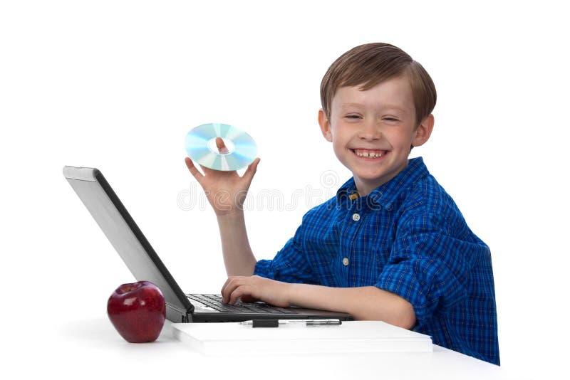 Junger kaukasischer Junge, der an Laptop mit einem CD arbeitet lizenzfreie stockfotografie