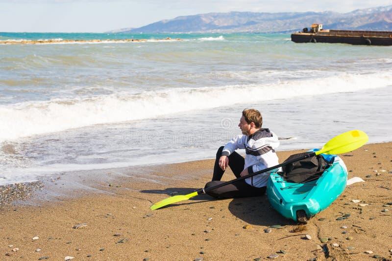 Junger kaukasischer Mann, der auf Strand mit Kajak sitzt stockbilder