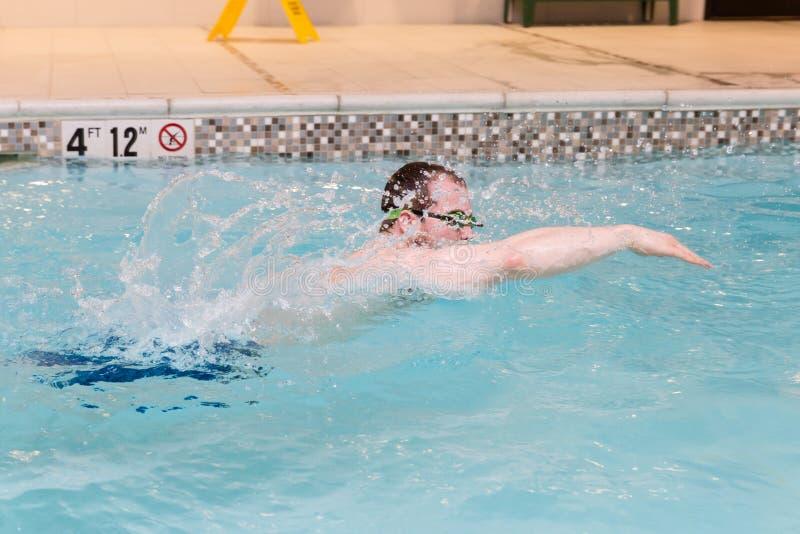 Junger kaukasischer Mann in der Bewegungsschwimmen im Pool stockfoto