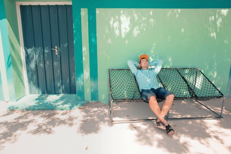 Junger kaukasischer Mann, der in einer angenehmen Trägheit der Hängematte des Wochenendenmorgens schwingt lizenzfreies stockfoto