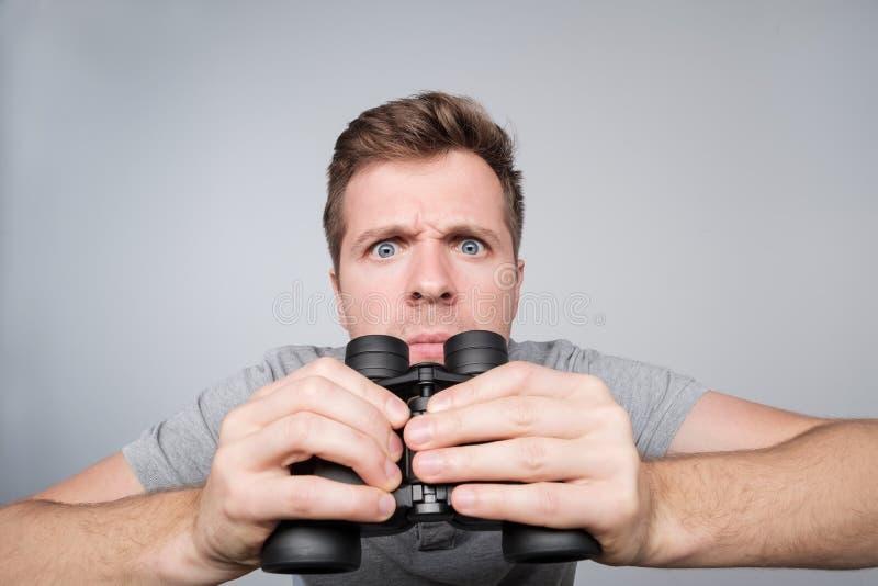 Junger kaukasischer Mann, der mit binokularem voran versuchen, einige wichtige Details zu sehen schaut lizenzfreies stockbild