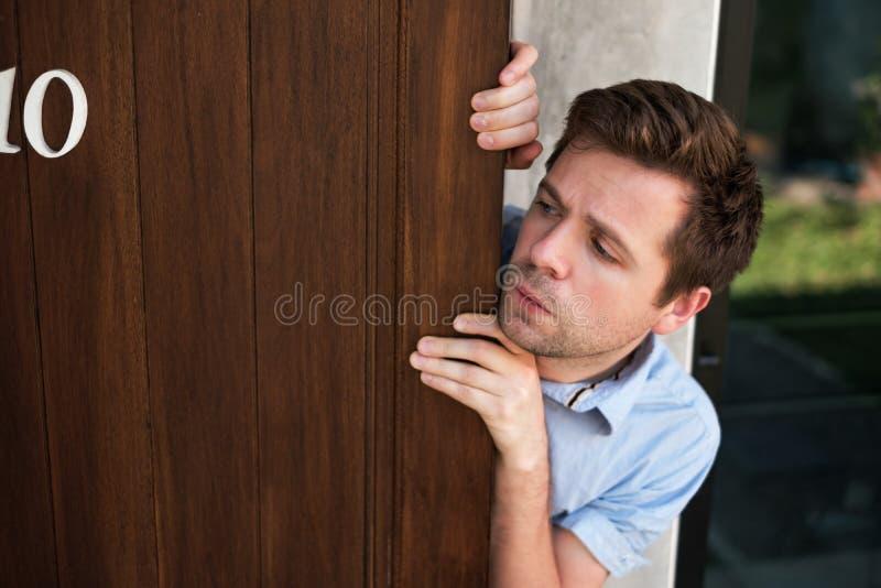 Junger kaukasischer Mann mit der Agoraphobie, welche heraus die Tür ausspioniert und schaut stockfotos