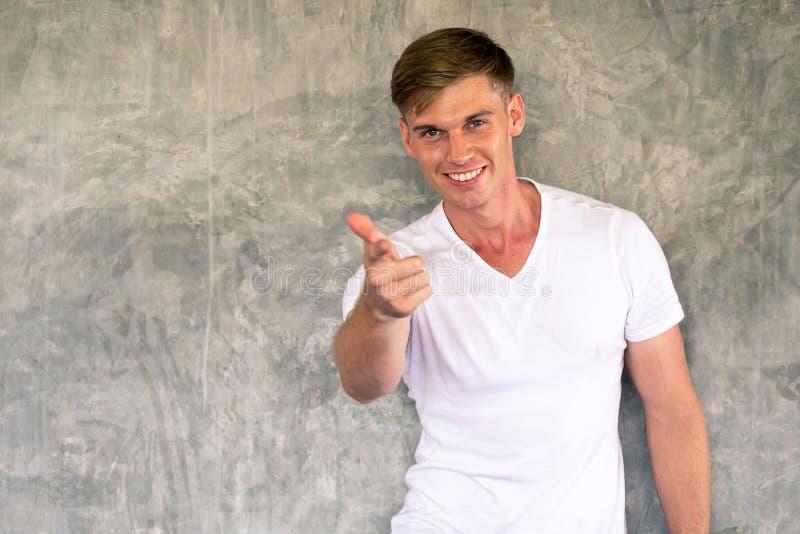 Junger kaukasischer Mann mit glücklichem und freundlichem Lächeln Finger auf Kamera zeigend lizenzfreie stockbilder